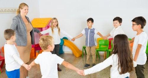 Niños haciendo pausas activas en clase agarrados de la mano formando un círculo.