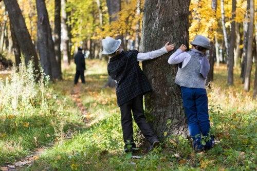 Niños detectives observando detrás de un árbol.