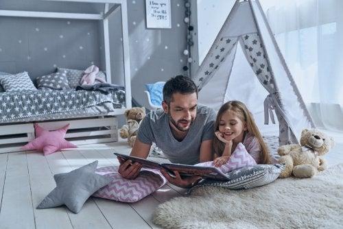 Padre leyendo con su hija tumbados en el suelo de la habitación cuentos personalizados para niños.