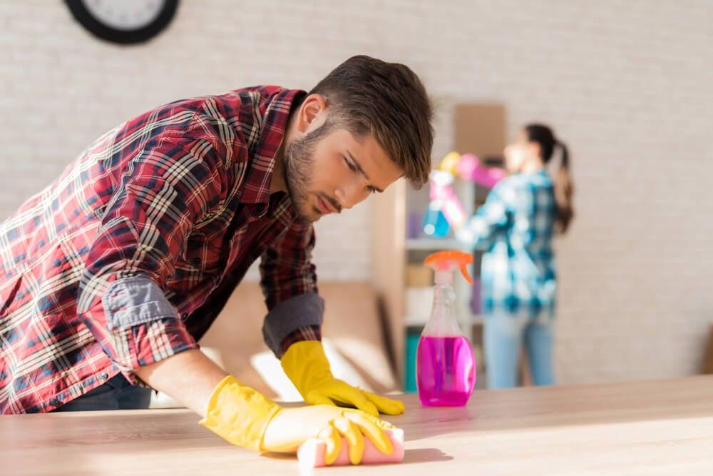 Pareja limpiando la casa juntos para reducir la carga mental de la mujer.