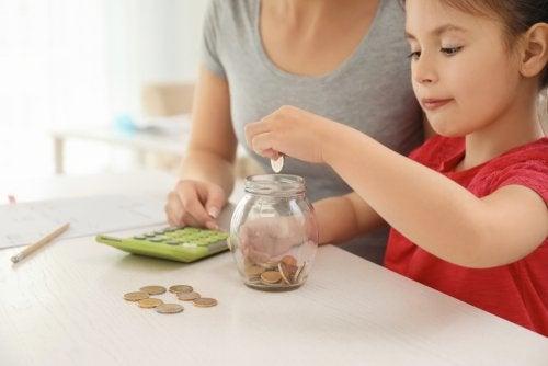 Niña metiendo monedas en un bote con su madre para aprender a ahorrar.