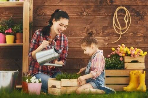 Madre con su hija regando algunas plantas del jardín,