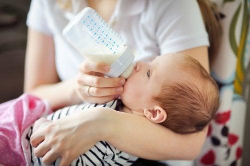 Madre asumiendo los riesgos de la lactancia artificial dándole un biberón a su bebé.