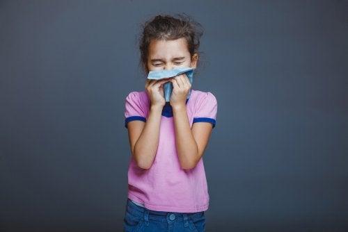 Niña sonándose la nariz con un pañuelo debido a que tiene alergia.