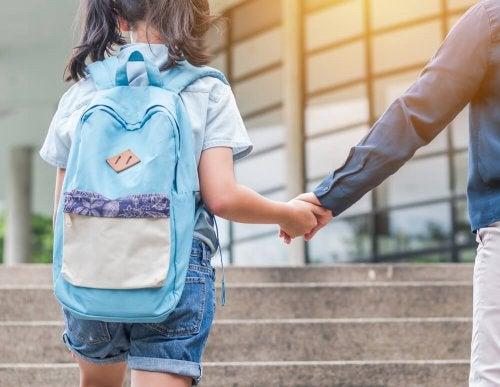 Niña yendo al colegio con uno de sus padres separados.