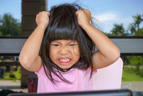 Niña enfadad tirándose del pelo.