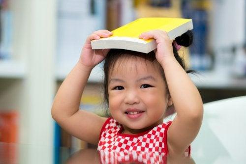 Niña bebé con un libro sobre la cabeza en una bebeteca.