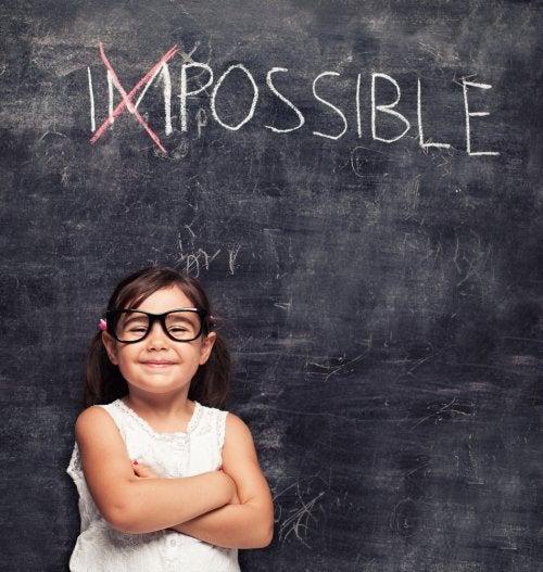 Niña optimista con un cartel detrás que tacha la palabra 'imposible'.