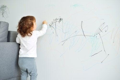 Niña pintando la pared del salón.