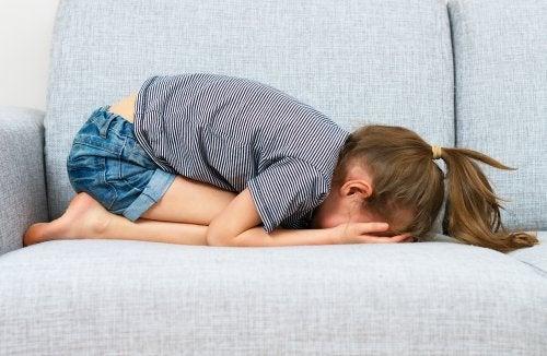 Niña llorando en el sofá con atiquifobia, miedo al fracaso.