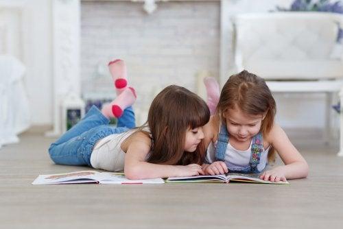 Niñas leyendo tumbadas en el suelo libros infantiles para mejorar la atención y la concentración.