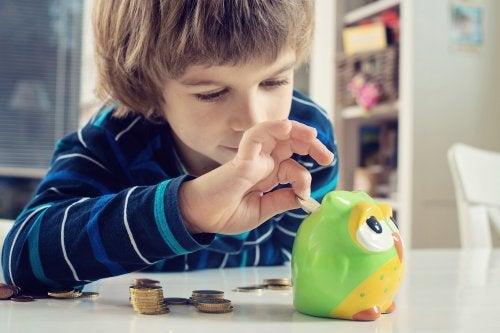 Niño metiendo dinero en la hucha como parte de una de las responsabilidades que puede asumir con su edad.