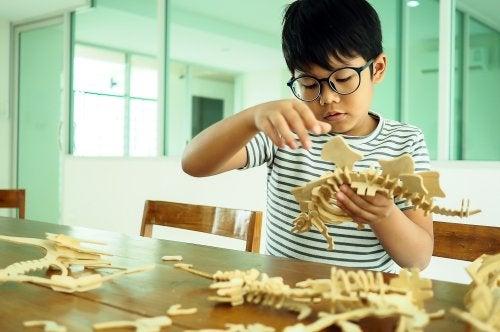Niño en clase haciendo una maqueta de un dinosaurio y teniendo en cuenta la importancia educativa de las diferencias individuales.