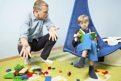 Niño con los juguetes tirados por la habitación siendo regañado por su padre para que los recoja.