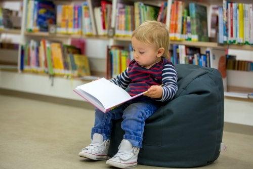 Niño leyendo un libro en una bebeteca.