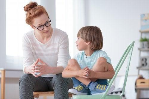 Madre hablando con su hijo para evitar que interrumpa constantemente.