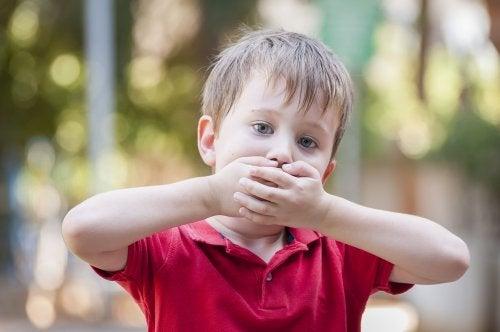 Niño con tartamudeo se tapa la boca porque le da vergüenza hablar.
