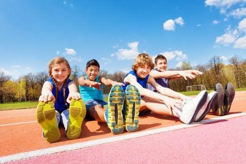 Niños haciendo estiramientos en atletismo como parte del entrenamiento y de los valores que transmite el libro Prohibido gritar.