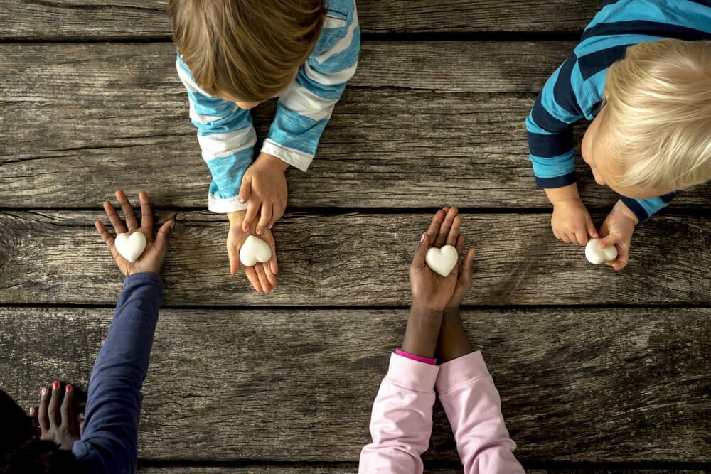 Niños con piedras en forma de corazón.