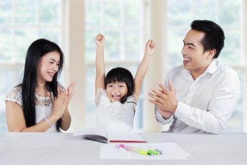 Padres felicitando a su hija por haber hecho bien las tareas escolares en casa de una forma divertida.