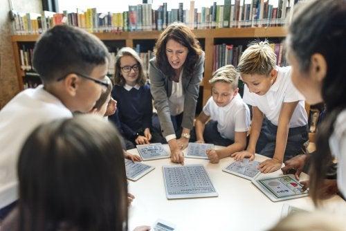Profesora trabajando con sus alumnos en la biblioteca escolar con tablets.