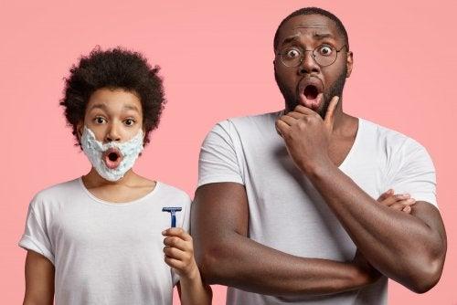 Adolescente con su padre aprendiendo a afeitarse.