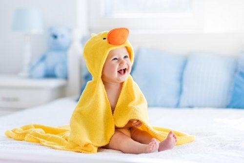 Bebé recién salido de la bañera tapado con su albornoz en forma de pato.