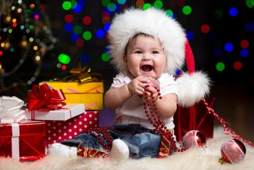 Bebé rodeado de todos sus regalos de Navidad.