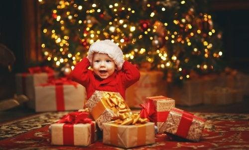 Bebé abriendo sus regalos de Navidad bajo el árbol decorado con luces.
