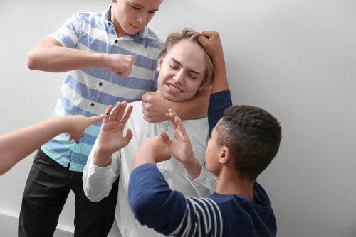 Chico sufriendo acoso escolar por parte de sus compañeros.