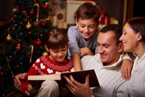 Familia leyendo libros sobre la Navidad junto al árbol.