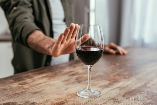 Hombre rechazando una copa de vino.