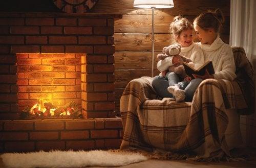 Madre leyendo cuentos para relajarse a tu hija junto a la chimenea.