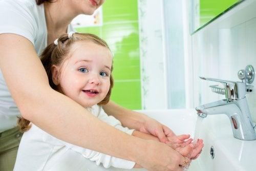 Madre e hija lavándose las manos para fomentar hábitos.