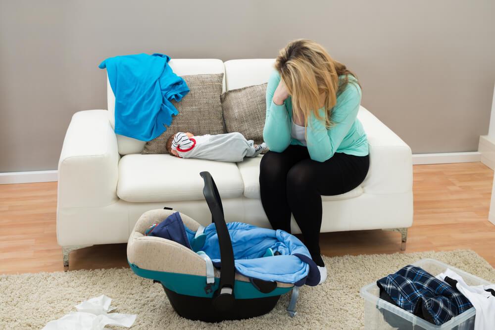 Mamá con depresión postparto con su bebé en el sofá.
