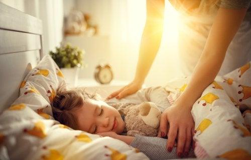 Mamá despertando a su hija por la mañana como parte del trabajo de las madres en casa.