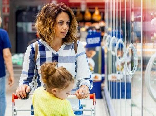 Mamá haciendo la compra en el supermercado con su hija.