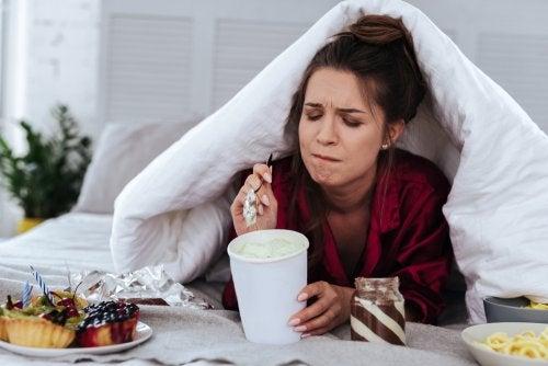 Mujer comiendo helado y dulces en la cama debido al comer emocional.