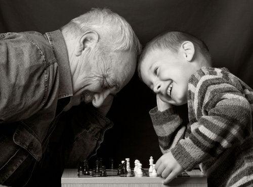 Niño jugando al ajedrez con su abuelo.