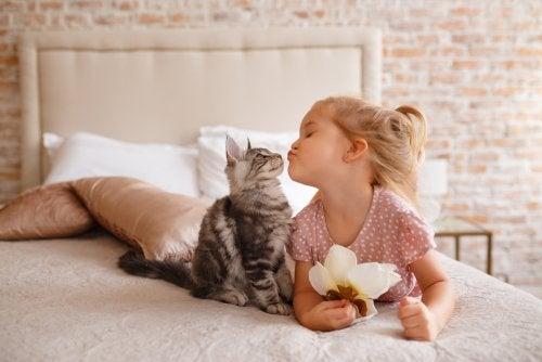 Niña dando un beso a su gato tras la adopción.