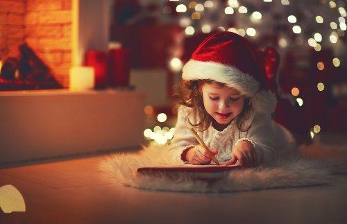 Niña escribiendo la carta a Papá Noel y los Reyes magos después de haber visto con sus padres el corto Una carta más corta.
