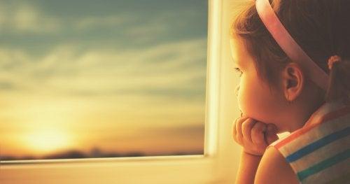 Niña mirando por la ventana expectante.