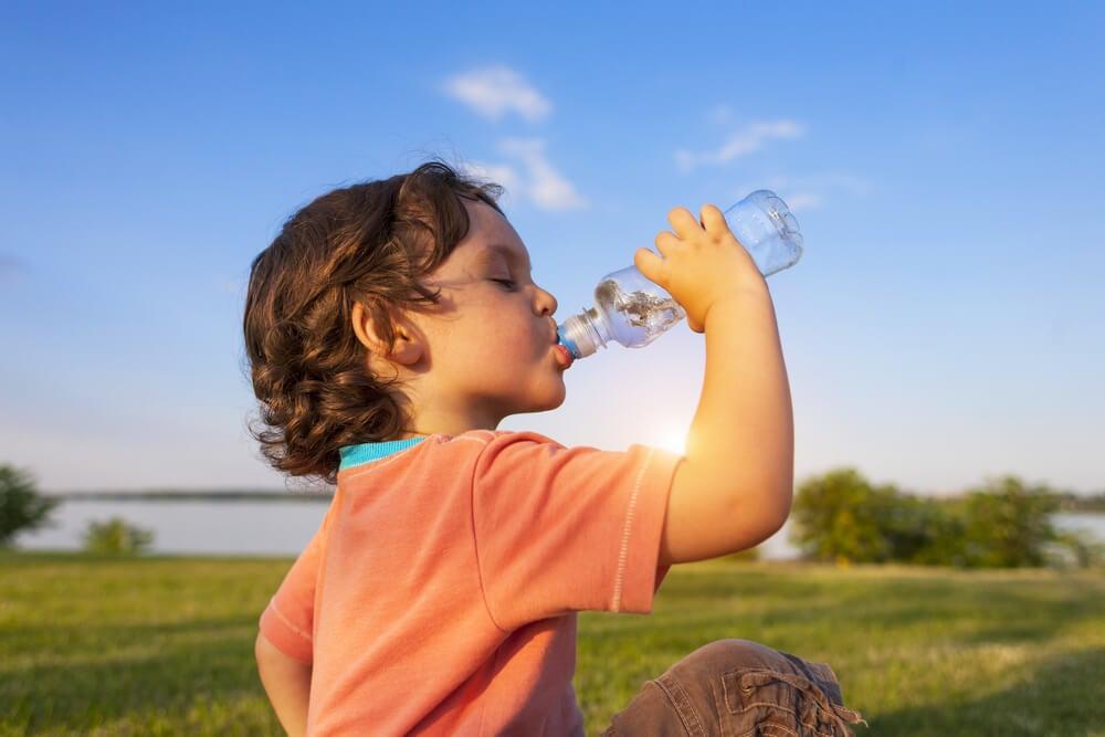 Niño bebiendo agua al aire libre.