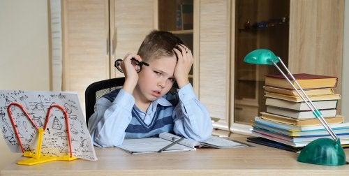Niño estudiando en su habitación con problemas y dificultad específica de aprendizaje.