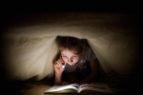 Niño leyendo cuentos infantiles modernos bajo el edredón con una linterna.