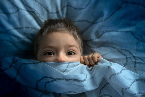 Niño metido en la cama con miedo al irse a dormir.
