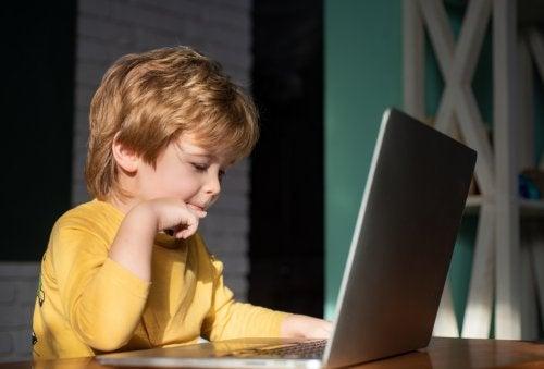 Niño en clases virtuales con el ordenador en casa demostrando la importancia de la tecnología en la vida de los niños.