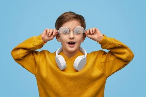 Niño sorprendido quitándose las gafas.