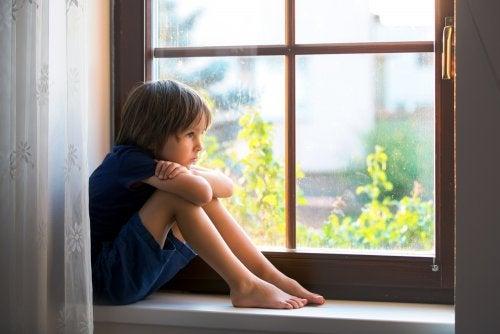 Niño triste mirando por la ventana.