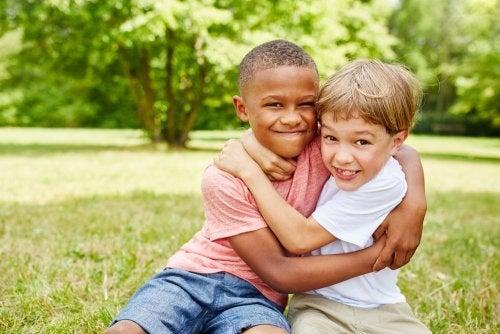 Niños amigos dándose un abrazo en el parque.